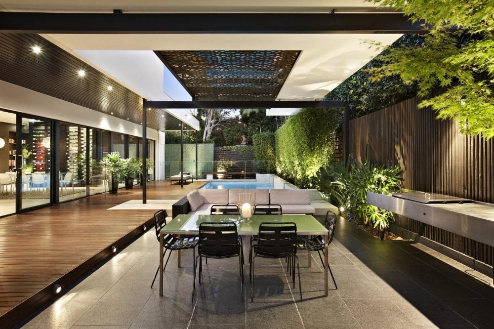 A patterned screen provides sunshade and a feature over this outdoor living space
