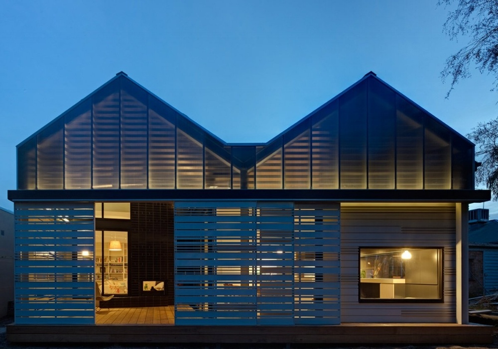 This house extension uses louvres to protect and provide a multi-use space