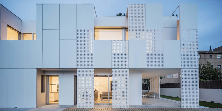 Perforated facade providing ventilation and privacy for homes.